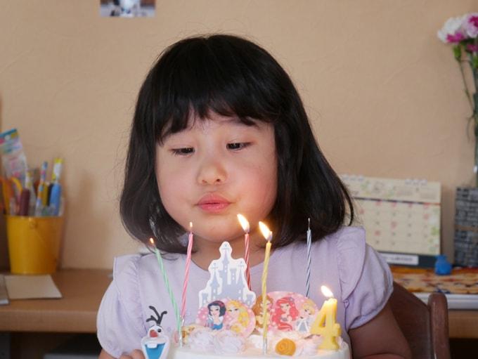 誕生日ケーキのロウソクを吹き消す女の子